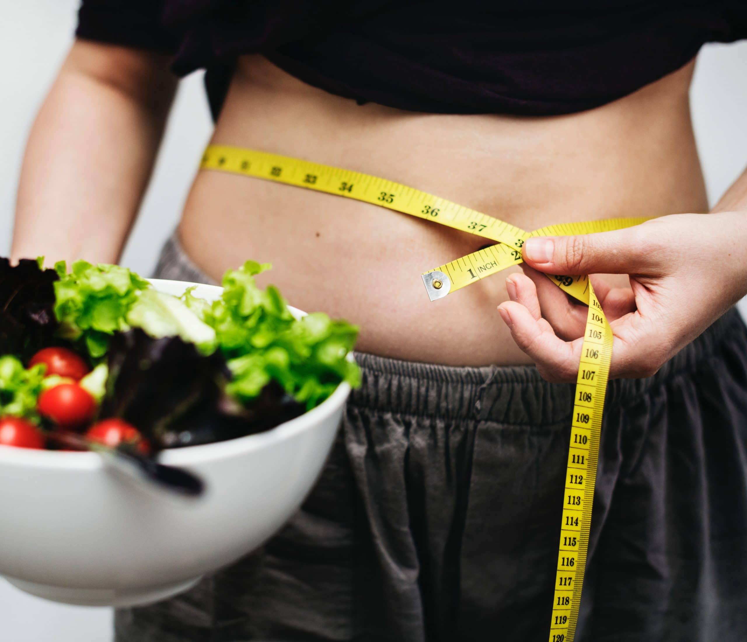 Pessoa segurando um pote de salada com uma mão e uma fita métrica ao redor da barriga com a outra.