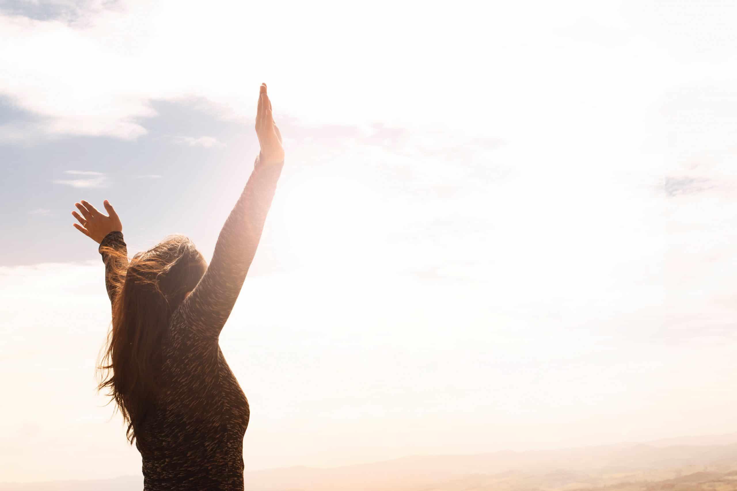 Mulher de lado com braços abertos e céu iluminado pelo sol de fundo