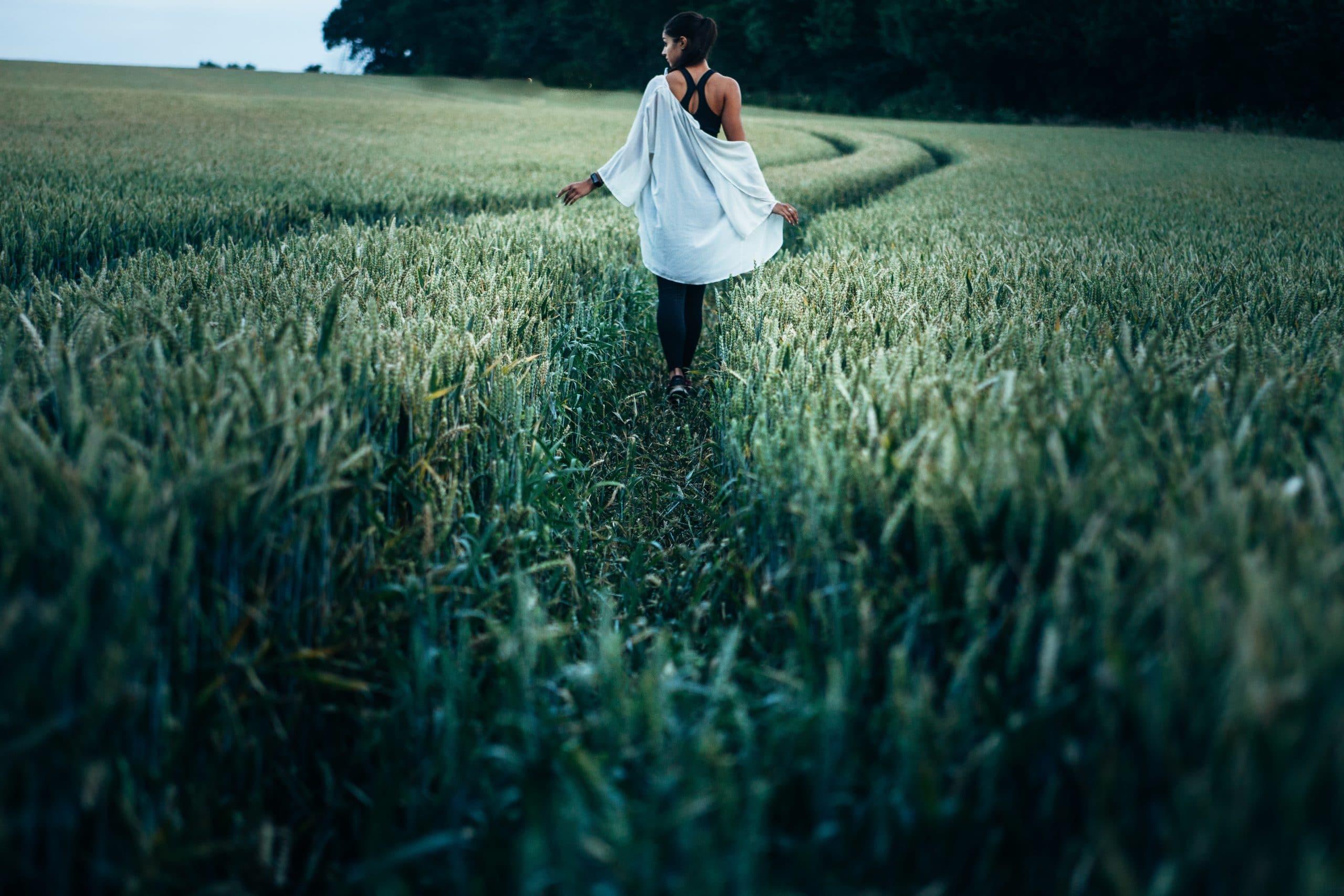 Mulher caminhando em campo com mata verde vista de costas