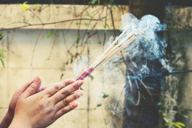 Mãos segurando incensos que soltam fumaça.