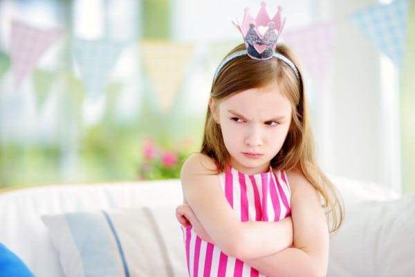 Menina branca, criança, sentada em um sofá, emburrada, com os braços cruzados e uma coroa prata na cabeça.