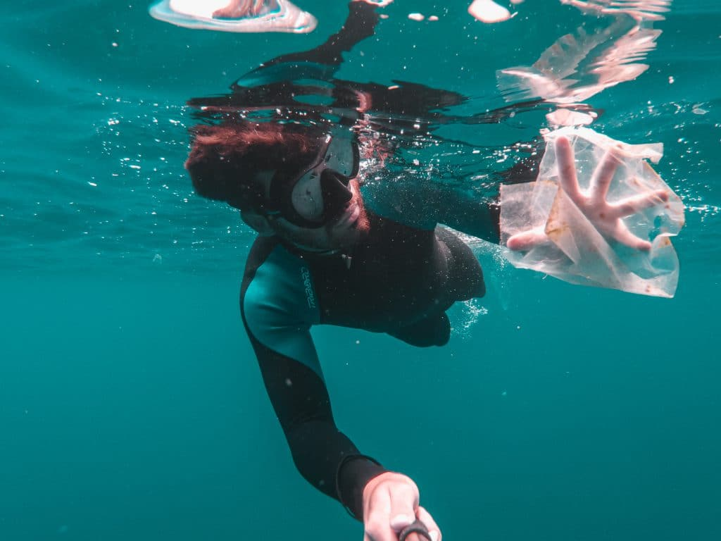 Homem mergulhando e pegando um pedaço de sacola de plástico que está no oceano.