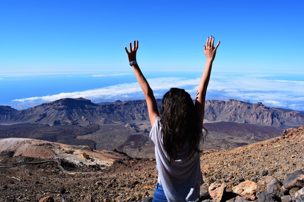 mulher de costas com braços para o alto e montanhas ao fundo