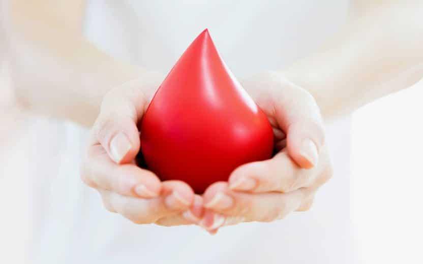 Mãos segurando uma estátua em formato de gota, vermelha, representando sangue.