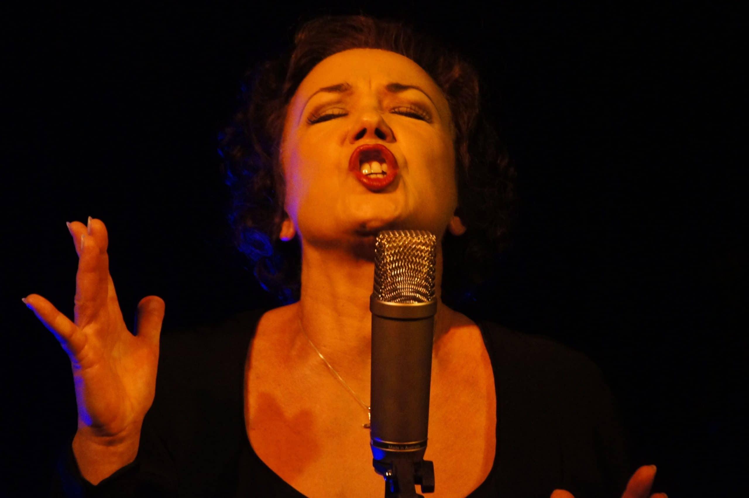 Mulher cantando cheia de emoção.