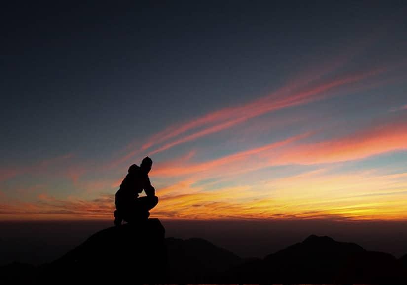 Homem sentado sobre uma pedra observando o pôr-do-sol.