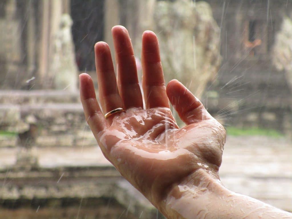 Uma mão estendida onde nela caem gotas de chuva.