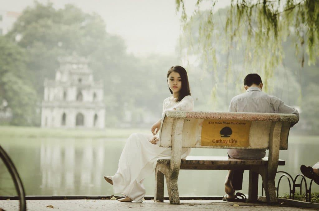 Mulher e homem, ambos asiáticos, sentados em um banco de praça, de frente para um lago. Os dois estão tristes e olhando em direções opostas