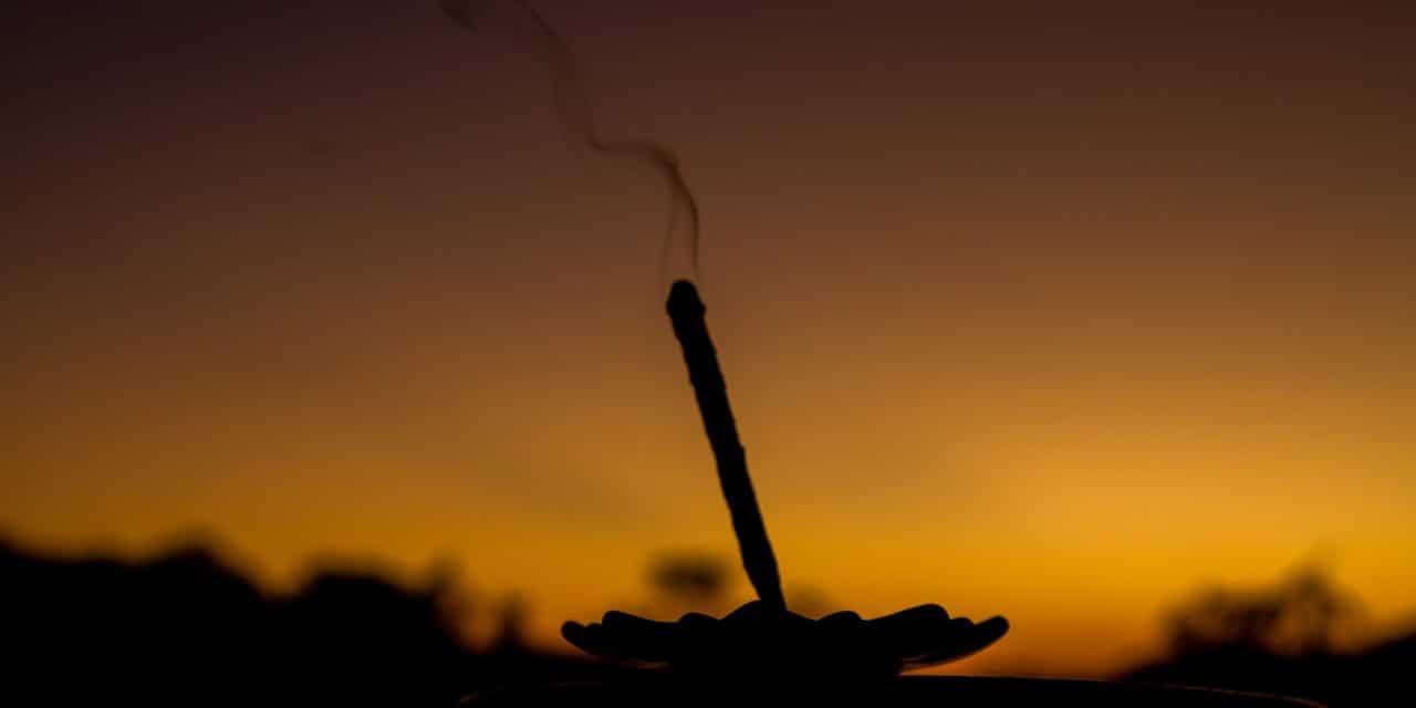 Silhueta de um incenso queimando ao pôr-do-sol.