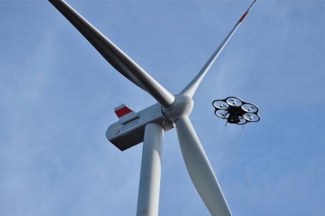 Drones sobrevoando moinho de vento.
