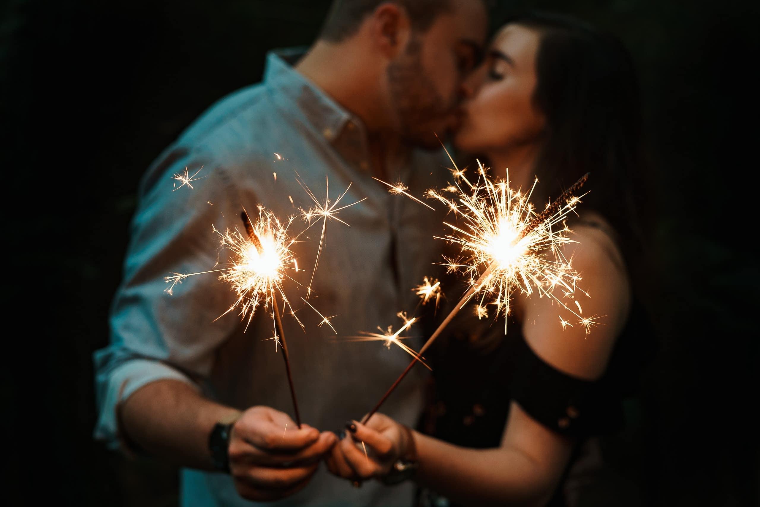 Casal se beijando com velas de ponto de luz na mão de cada um