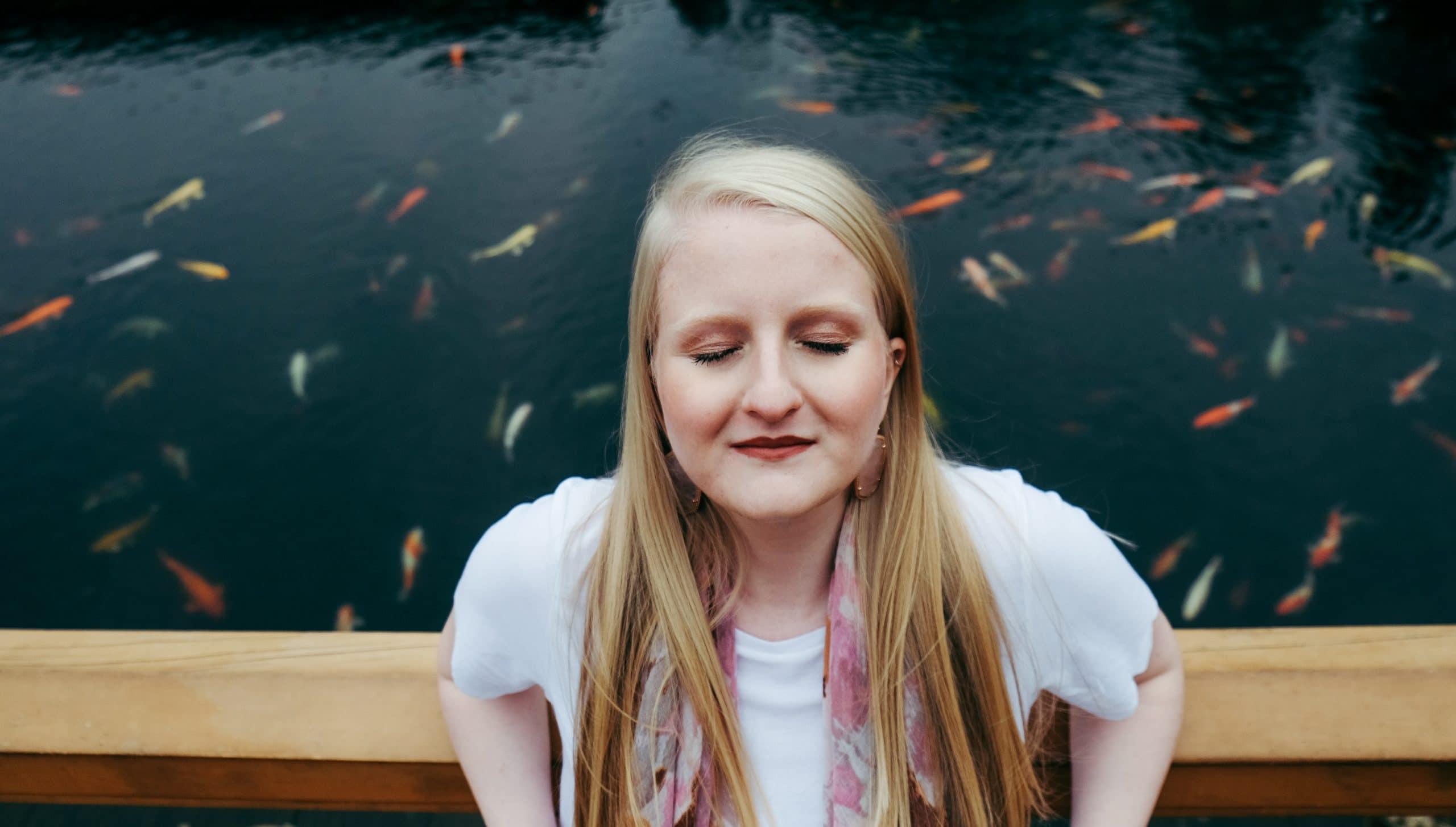 Mulher de olhos fechados de frente com rio e peixinhos ao fundo