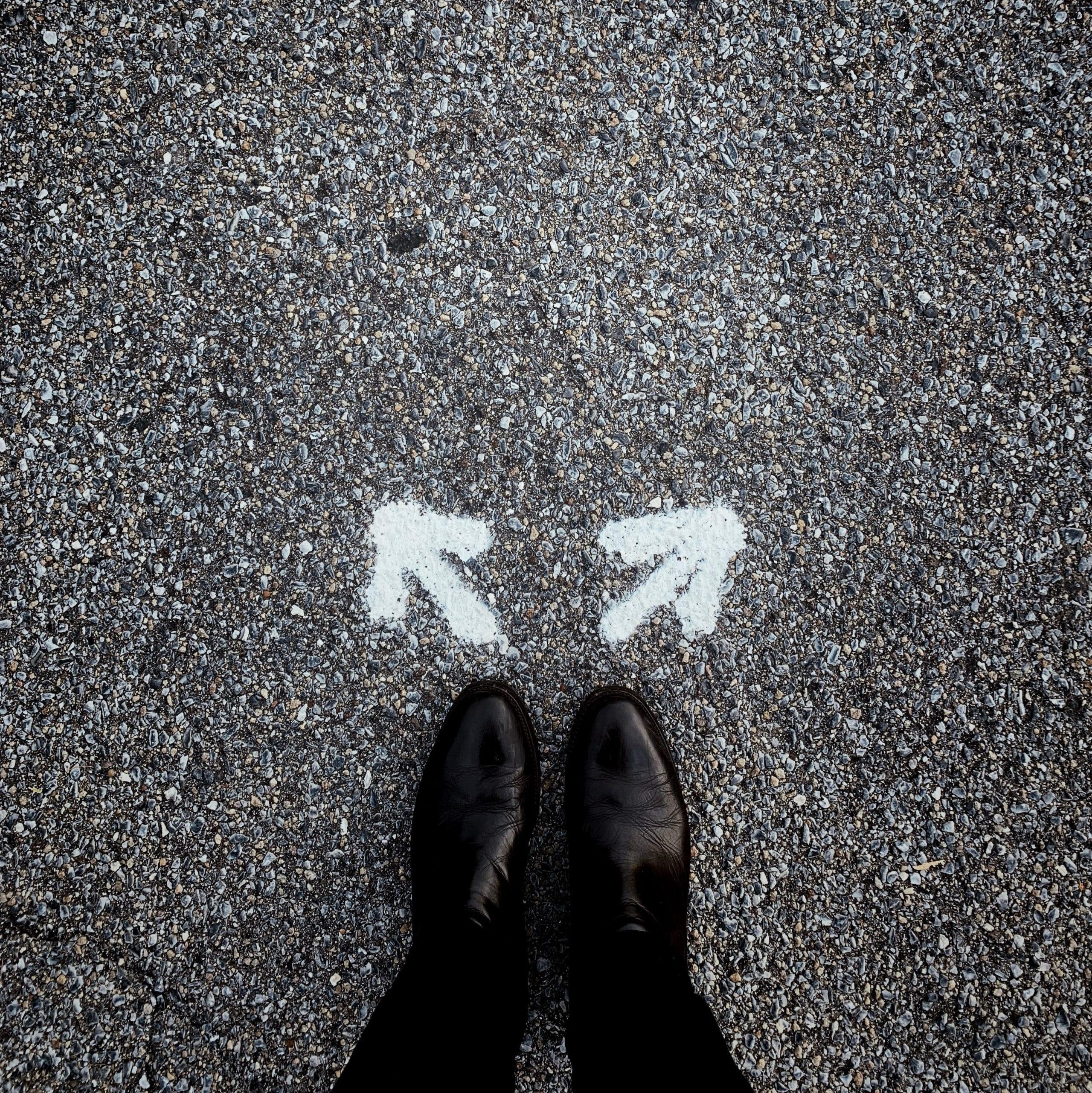 Pés parados perto de duas setas apontando para direções distintas no asfalto.