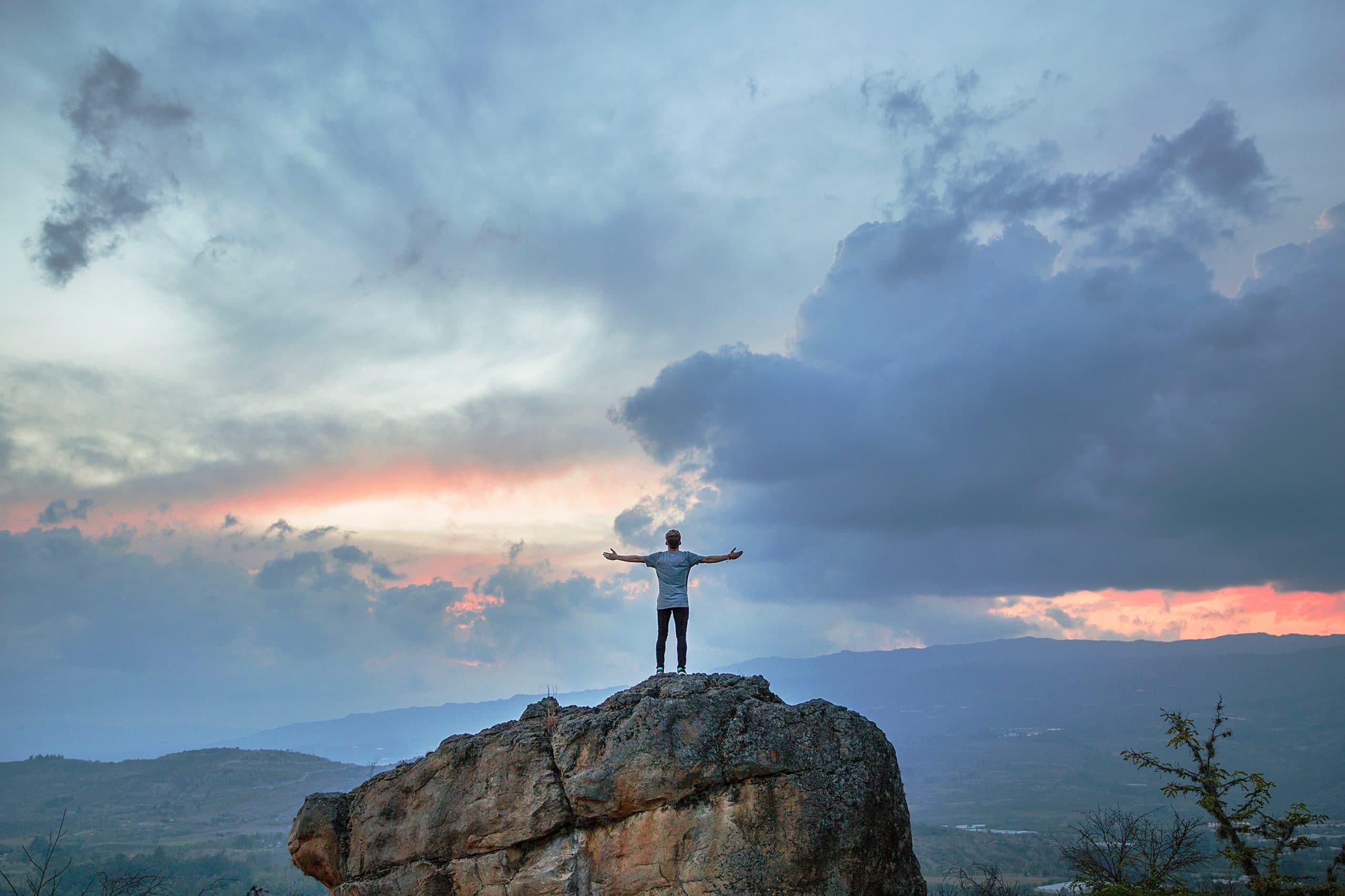 Homem em cima de pedra grande com céu com nuvens de fundo