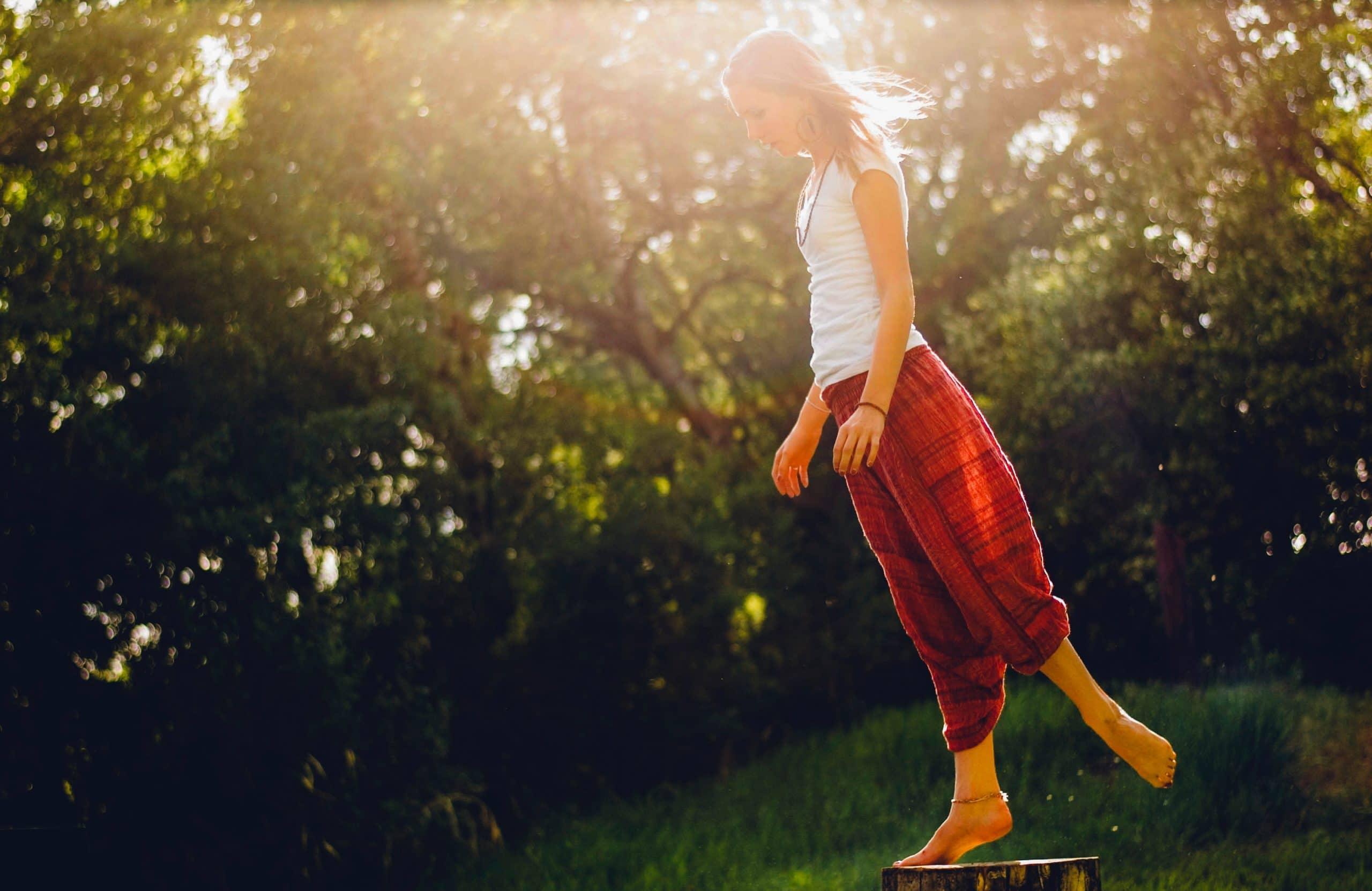 Mulher com roupas leves equilibrando-se em um tronco de árvore em meio à natureza.