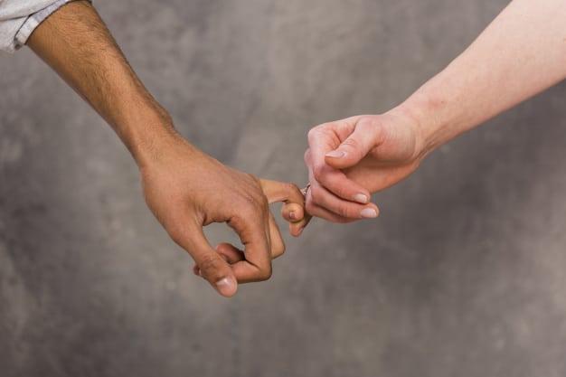 Mão de um homem com o dedo mindinho entrelaçado com o de uma mulher.