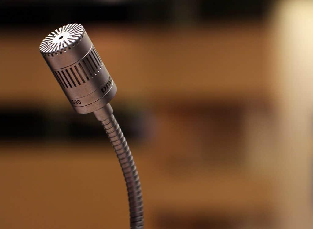 Microfone prateado com um fundo desfocado.