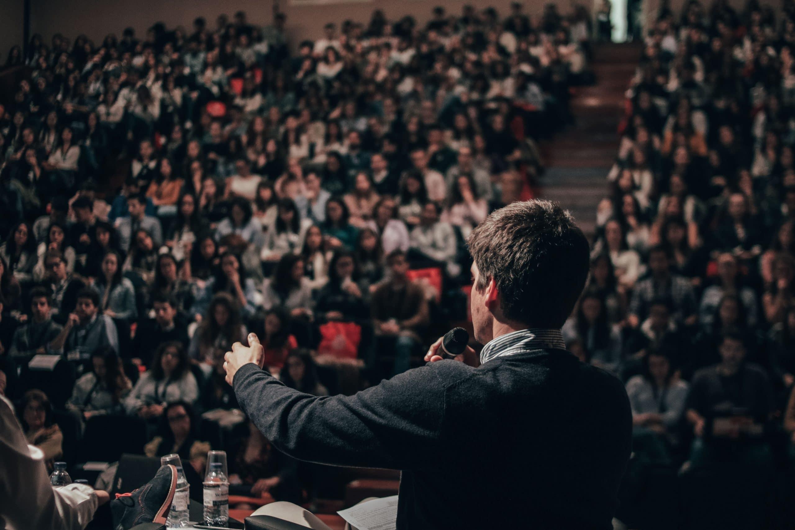 Homem dando discurso para plateia lotada.