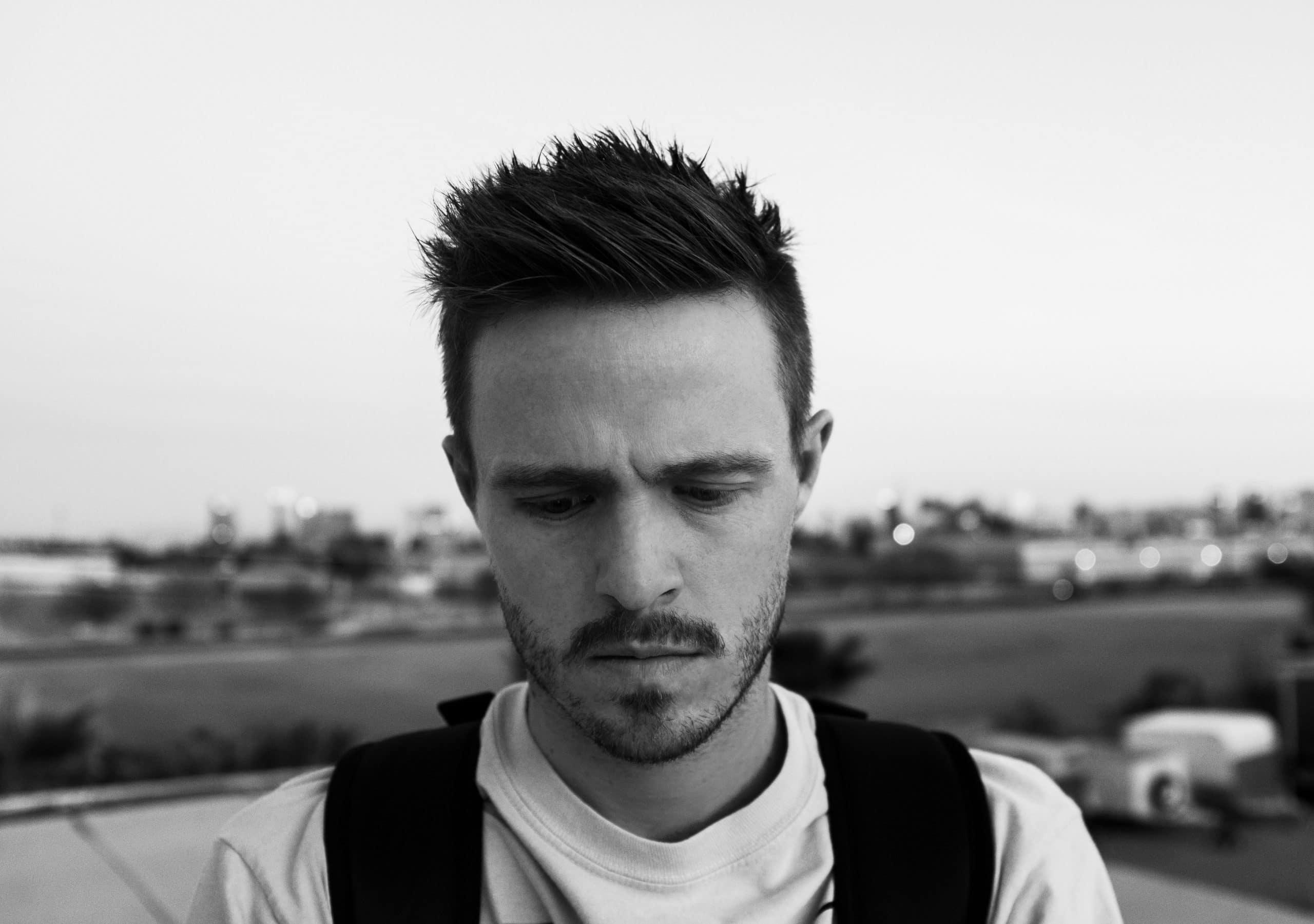 Rapaz visto de frente triste com campo de fundo em preto e branco