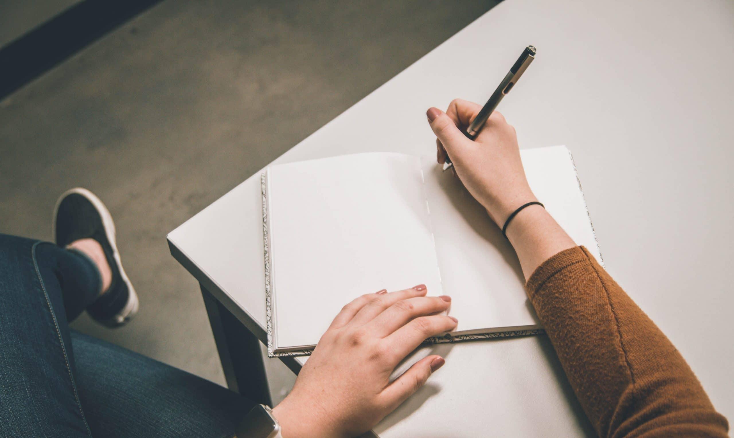 Mãos sobre caderno com caneta para escrever e pernas cruzadas na lateral