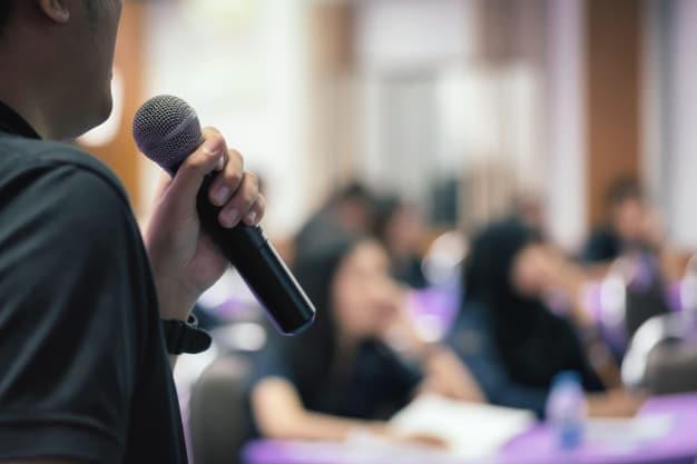 Homem de perfil falando ao microfone para uma plateia.