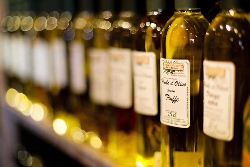 Vidros de azeite de oliva enfileirados em um mercado.