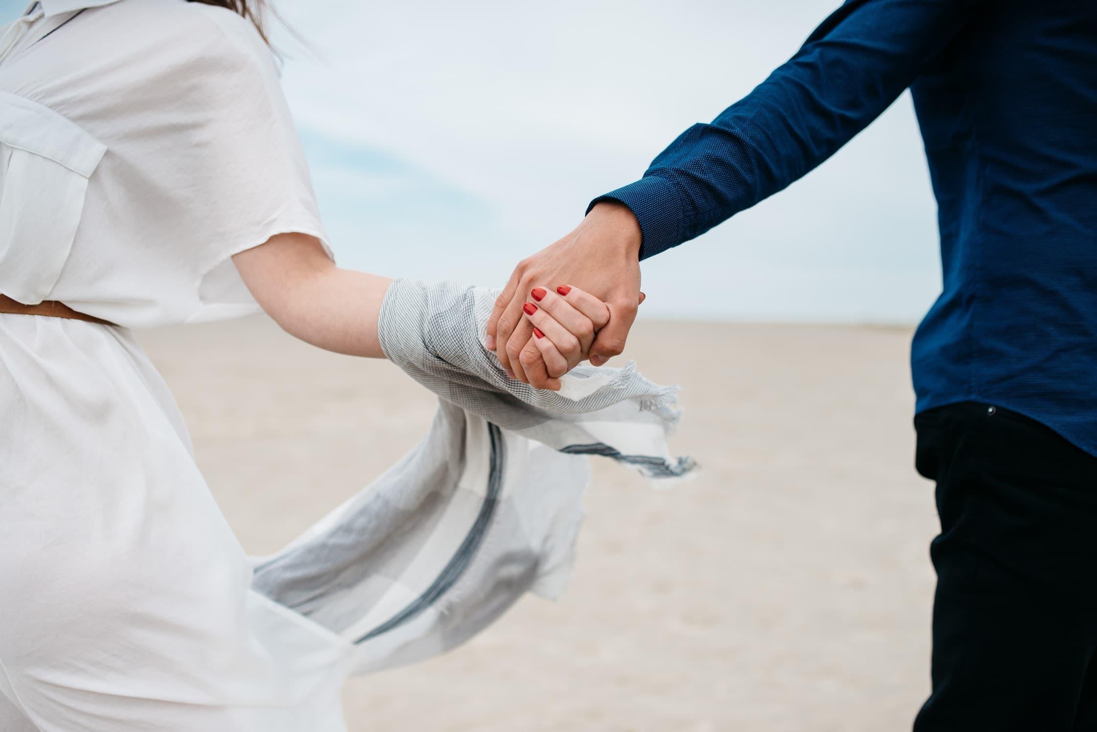 Mãos de casal dadas com fundo de areia