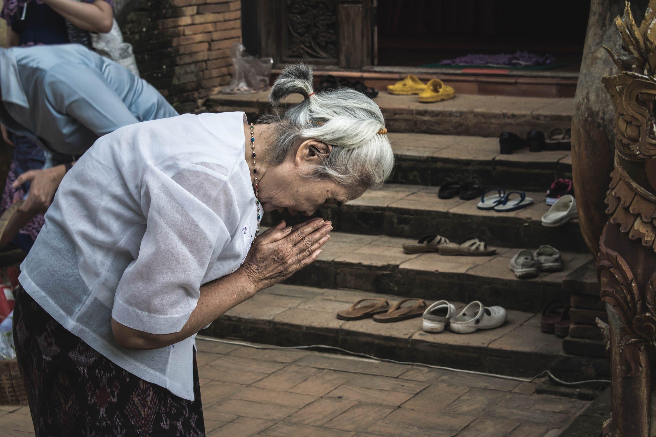 Senhora idosa inclinada com as mãos em sinal de oração.