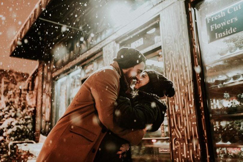 Casal se beijando com a neve caindo em cima deles.