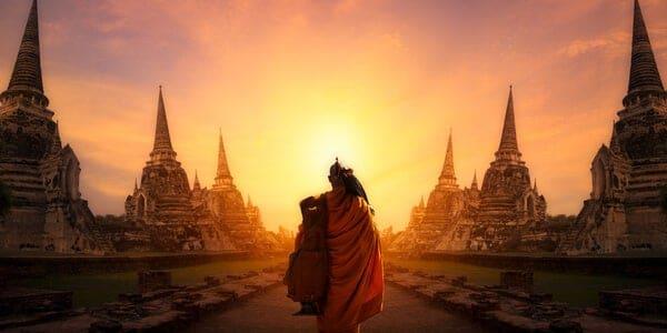 Monge caminhando entre templos em direção ao pôr-do-sol.