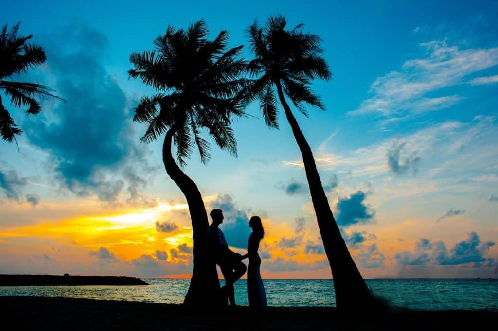 Casal em clima de romance aproveitando o pôr do sol.