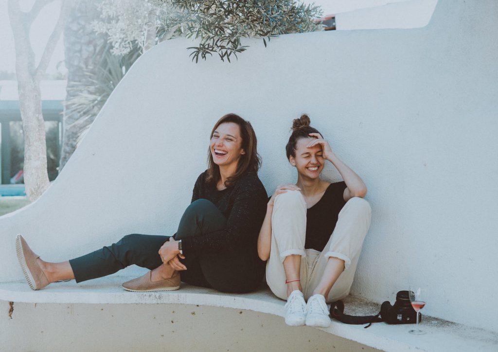 Duas mulheres brancas, jovens, ambas rindo, sentadas a bera de uma piscina vazia.