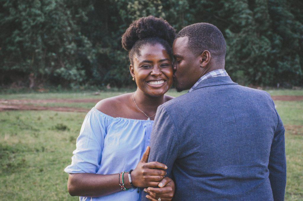 Casal de homem e mulher, ambos negros, sorridentes e se abraçando.