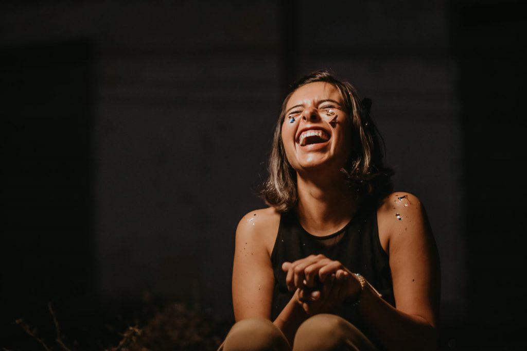 Mulher jovem, morena, sentada no chão, rindo, coberta de confetes.
