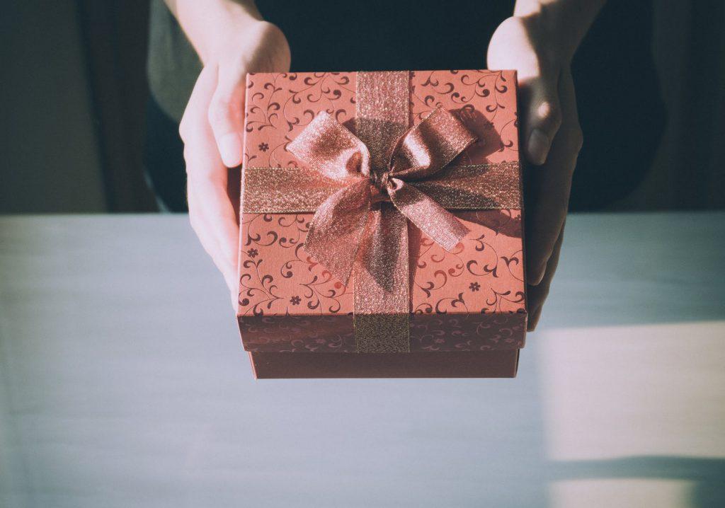 Mãos de pessoa branca, entregando uma caixa de presente