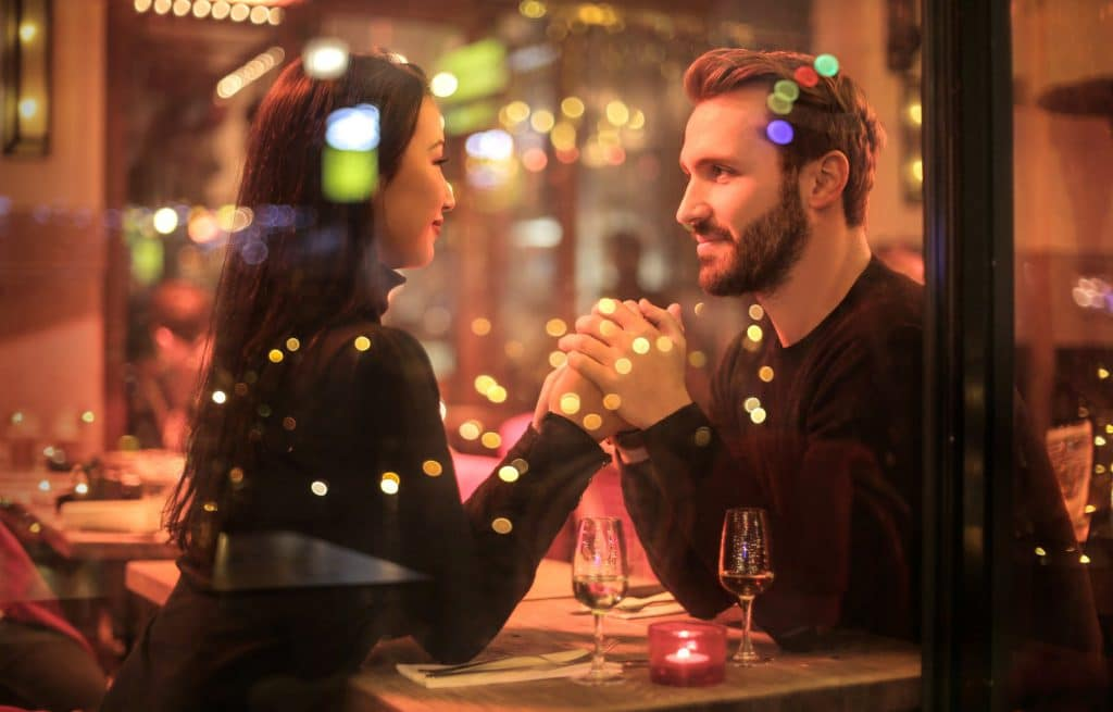 Casal de homem branco e mulher asiática, sentando na mesa de um restaurante, de mãos dadas, olhando um nos olhos do outro