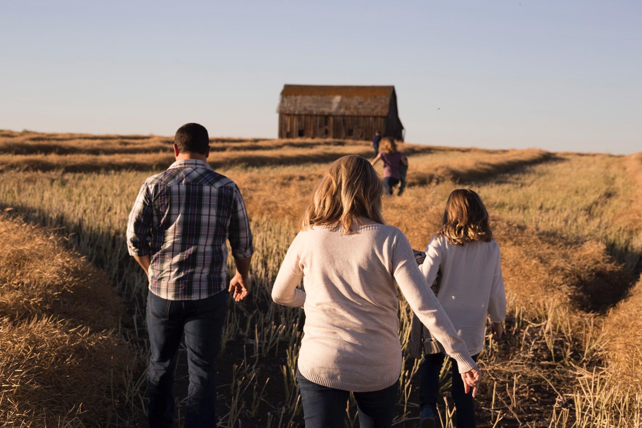 Família andando em campo seco de costas sentido celeiro