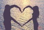 Casal fazendo coração com os braços com o mar de plano de fundo