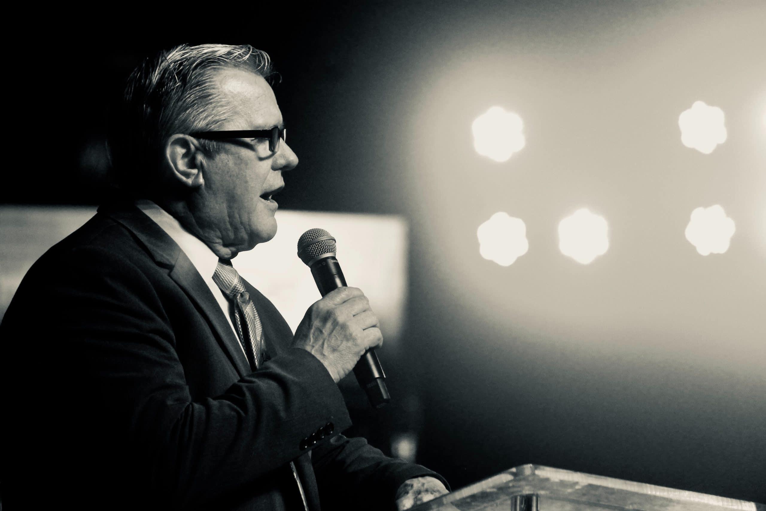 Homem fazer discurso no microfone.