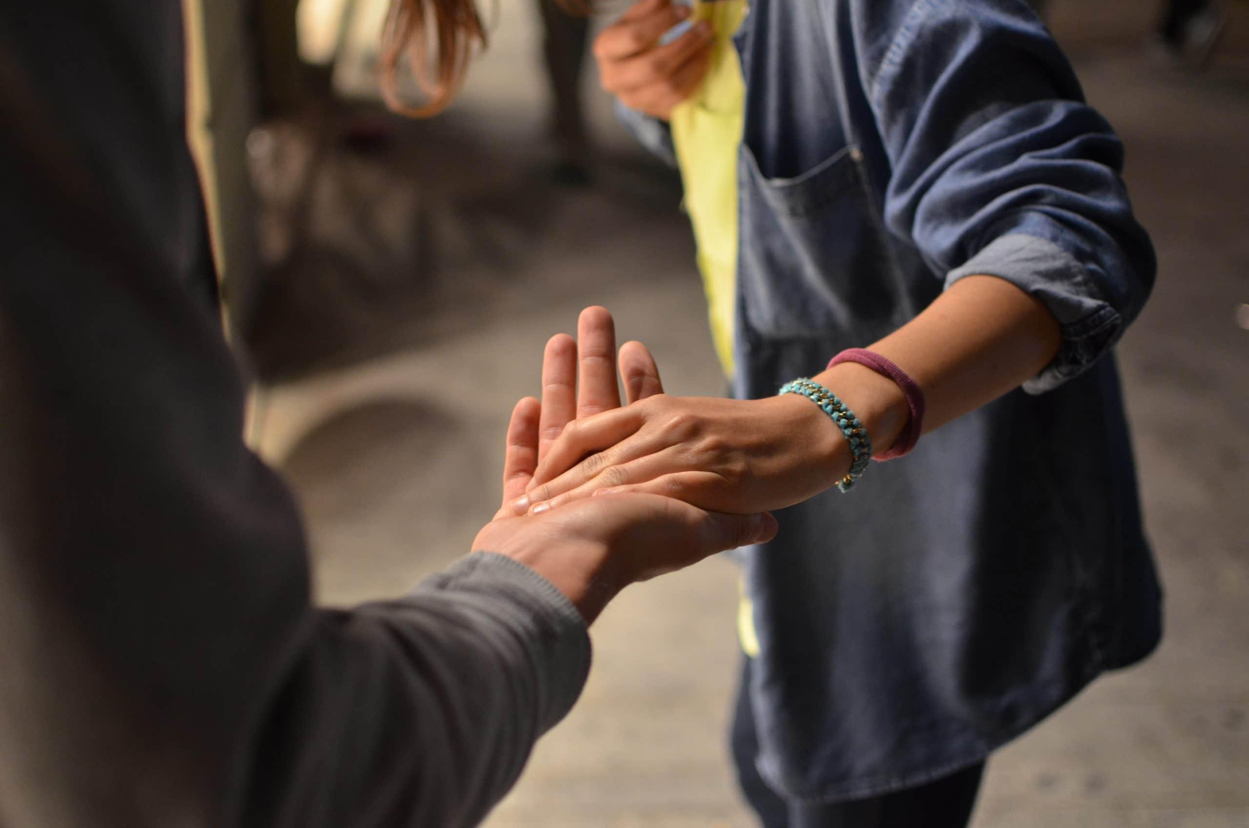 Duas pessoas dando as mãos.