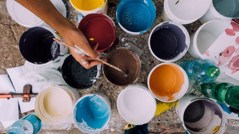 Mão com pincel na mão e latas de tinta vista de cima