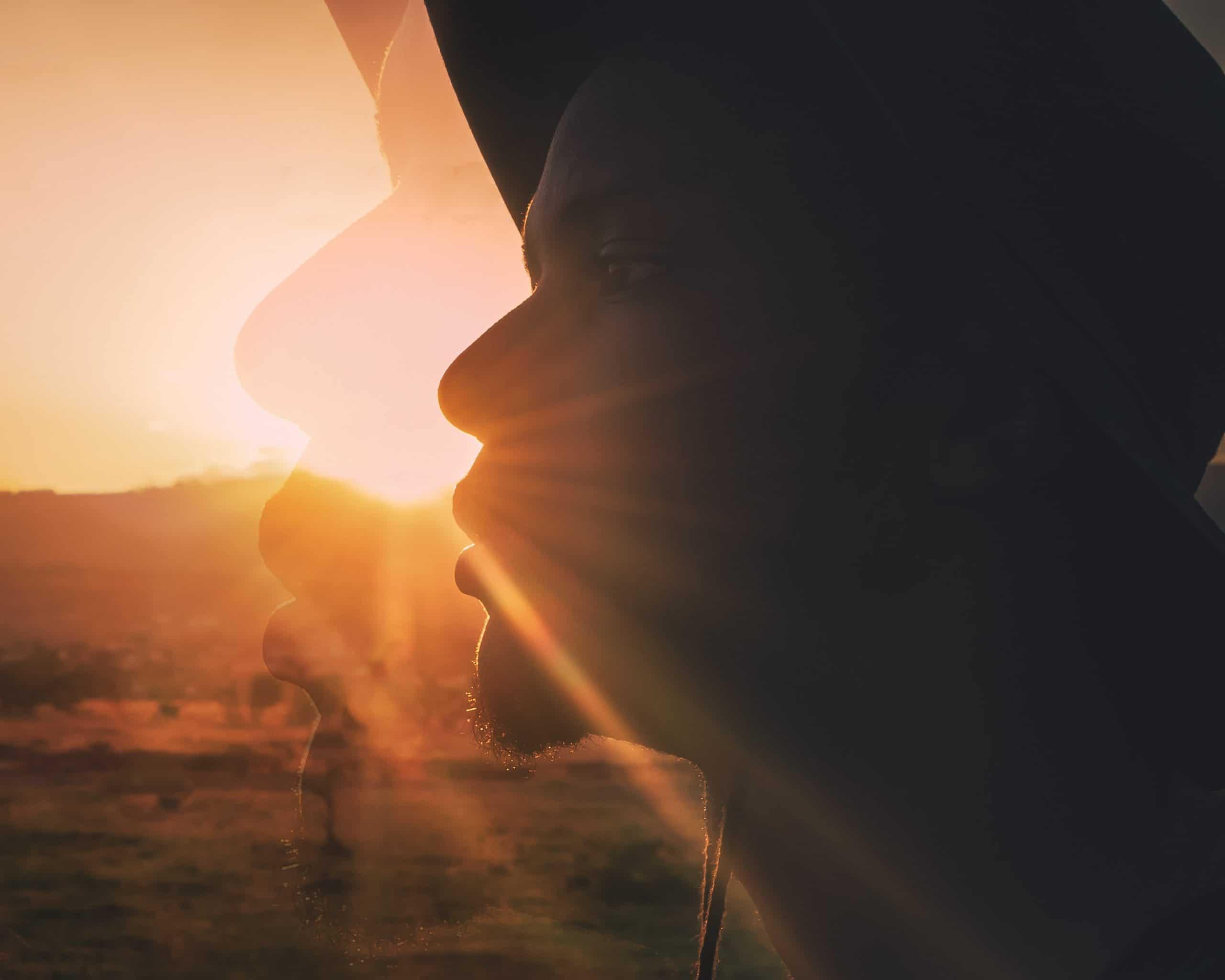 Rosto visto de lado com sol refletido de frente para a foto