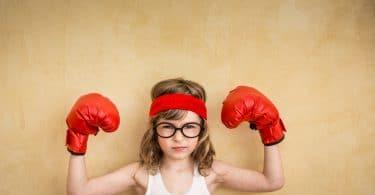 Menina com luvas de boxe e as mãos levantadas em sinal de força.