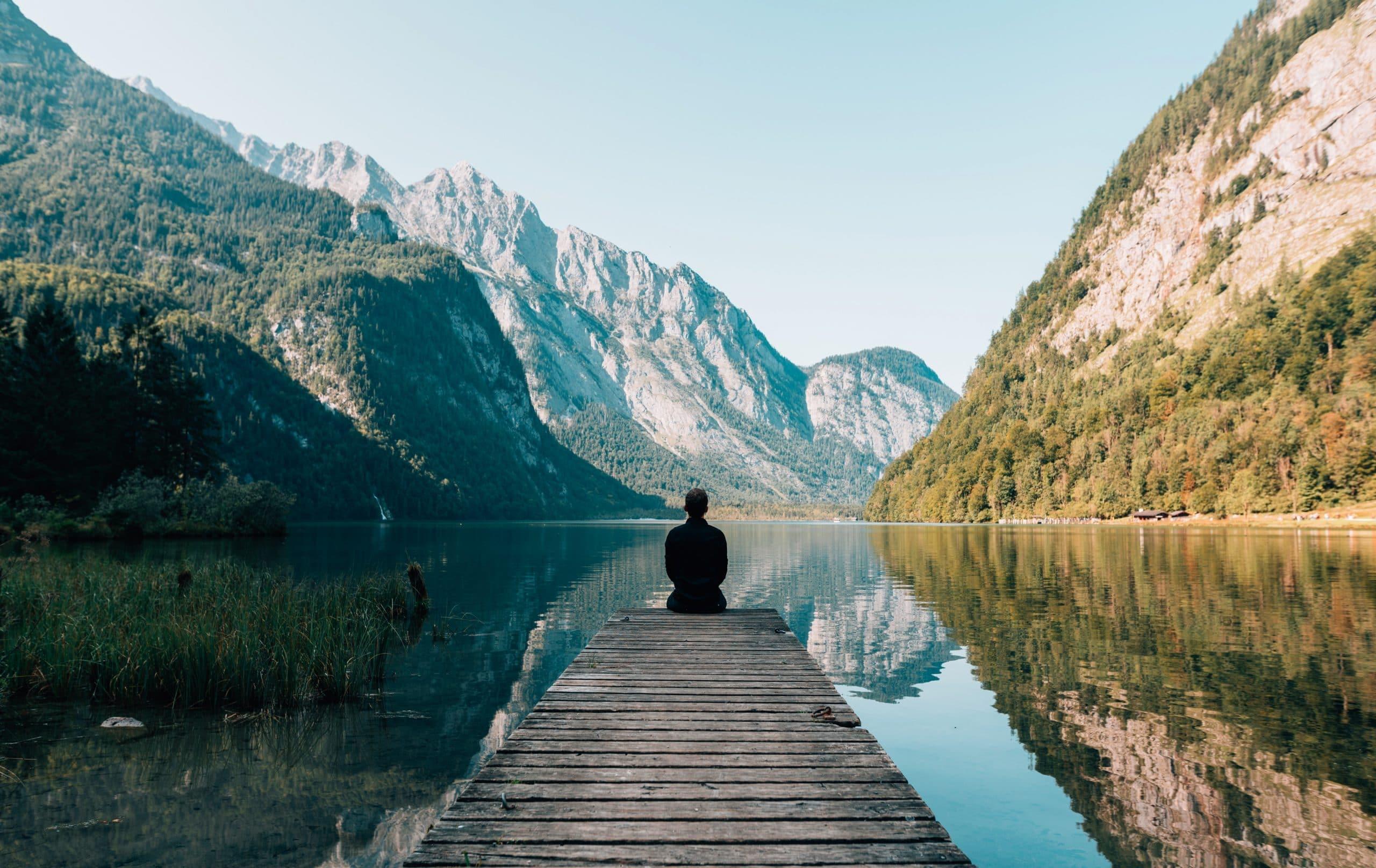 Homem sentado em ponte com lago e paisagem de montanhas ao fundo