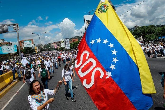 Manifestação de pessoas e mulher à frente com bandeira da venezuela