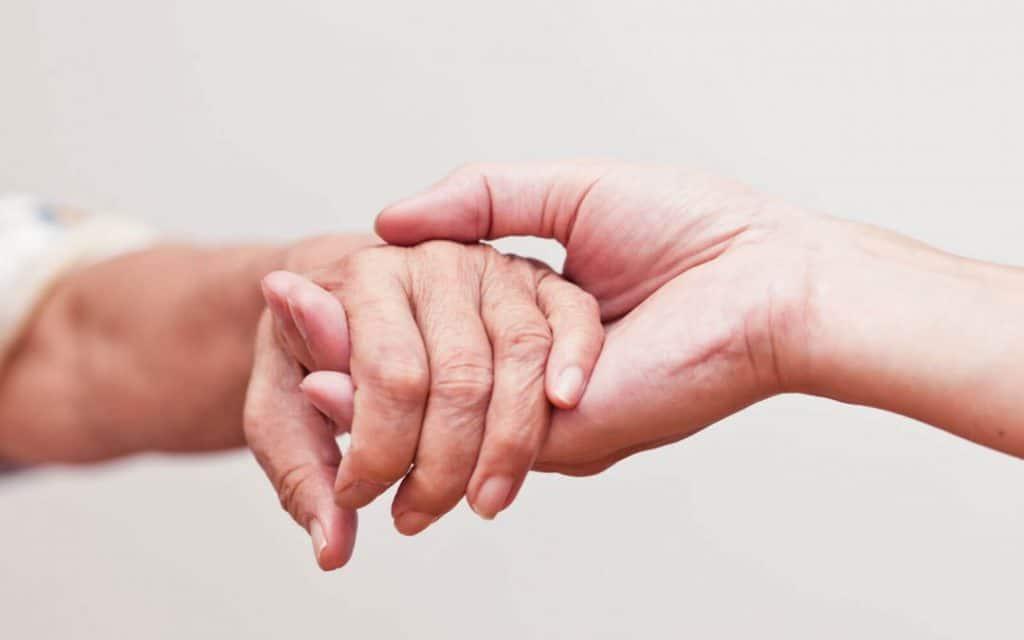 Mãos de duas pessoas brancas, uma pegando na outra