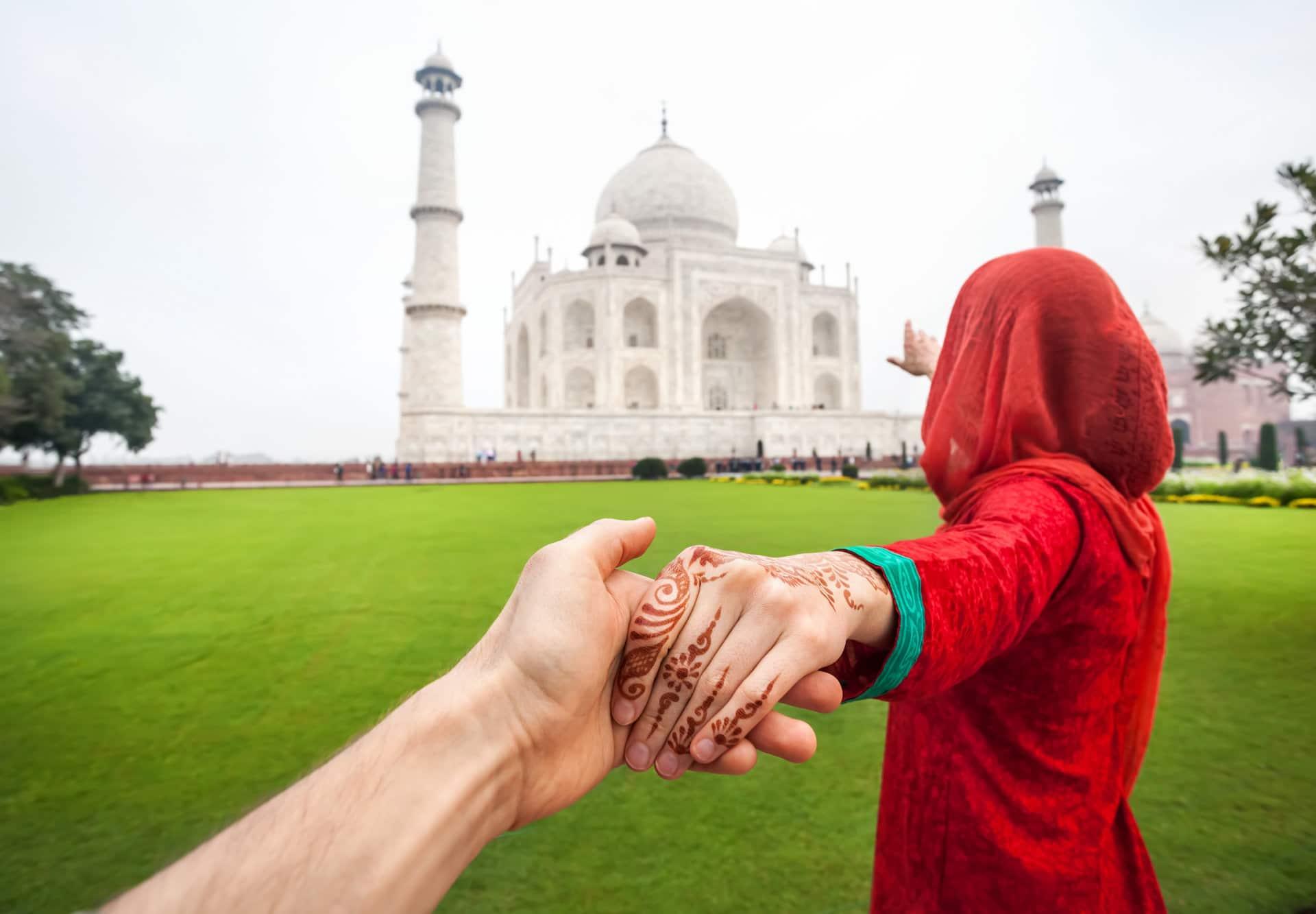 Casal de mãos dadas apontando para o Taj Mahal,