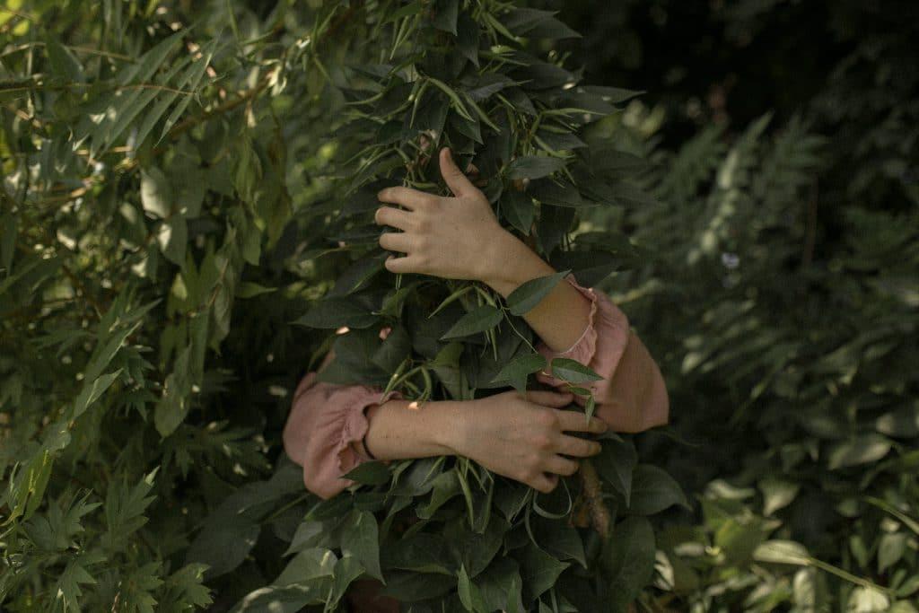 Pessoa abraçando uma árvore.