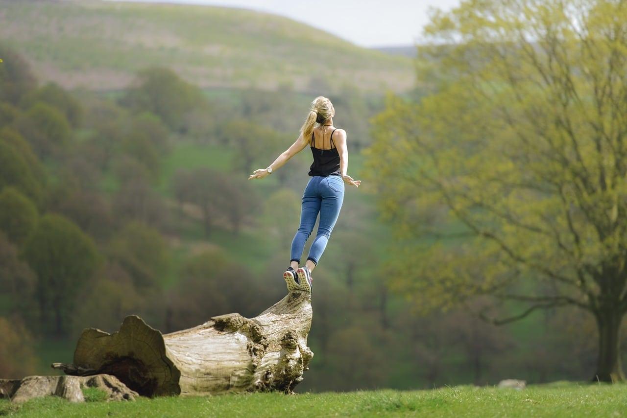Mulher loira na natureza em cima de um tronco de árvore caído no chão. Ela usa uma calça jeans azul e uma regata preta, está com os braços abertos de costas.