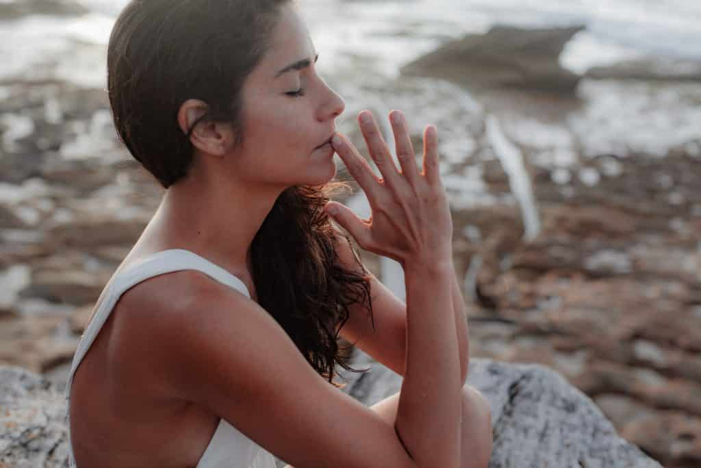 Mulher sentada, de olhos fechados, com as mãos juntas em frente ao rosto.